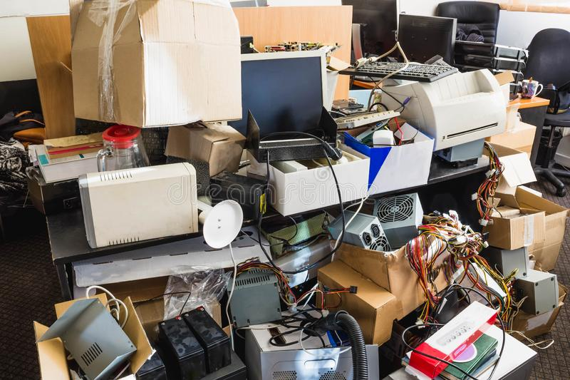 A messy desktop with stacks of files and other documents, all kind of office supplies and part of a keyboard. stock photos