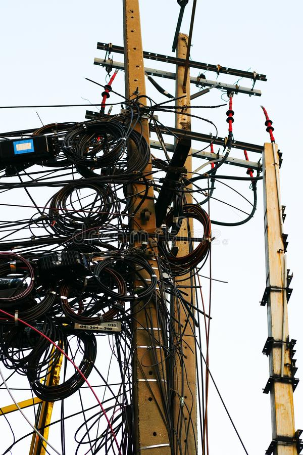 Messy electrical and telecommunication wire in Bankgkok, Thailand. Messy electrical and telecommunication wire is hanging on the pole in Bankgkok, Thailand stock images