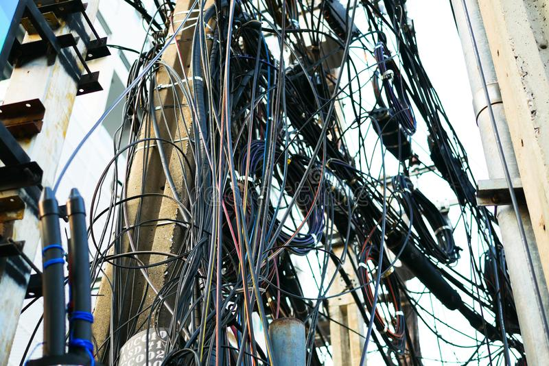 Messy electrical and telecommunication wire in Bankgkok, Thailand. Messy electrical and telecommunication wire is hanging on the pole in Bankgkok, Thailand stock photo