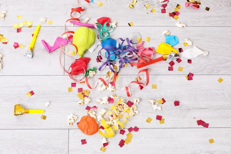Messy floor with popcorn, streamers, confetti and used balloons after party. Top view stock photo