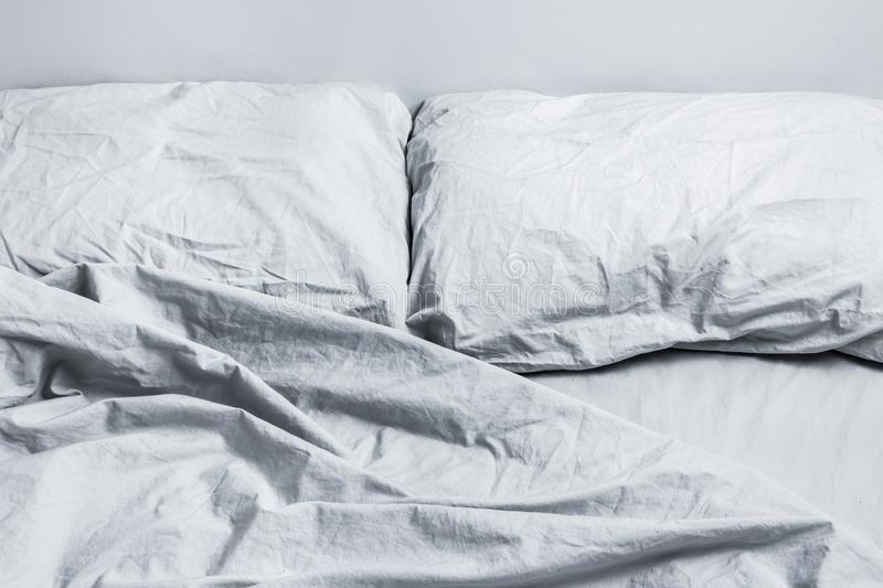 Messy gray bed linen. Bed with two pillows in daylight stock image