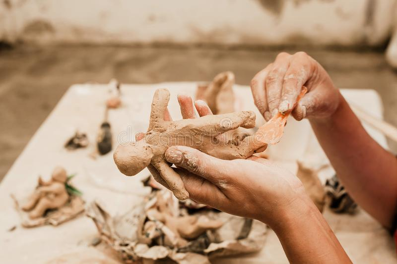 Messy hands working clay, close up and focus on potters palms with pottery royalty free stock photography