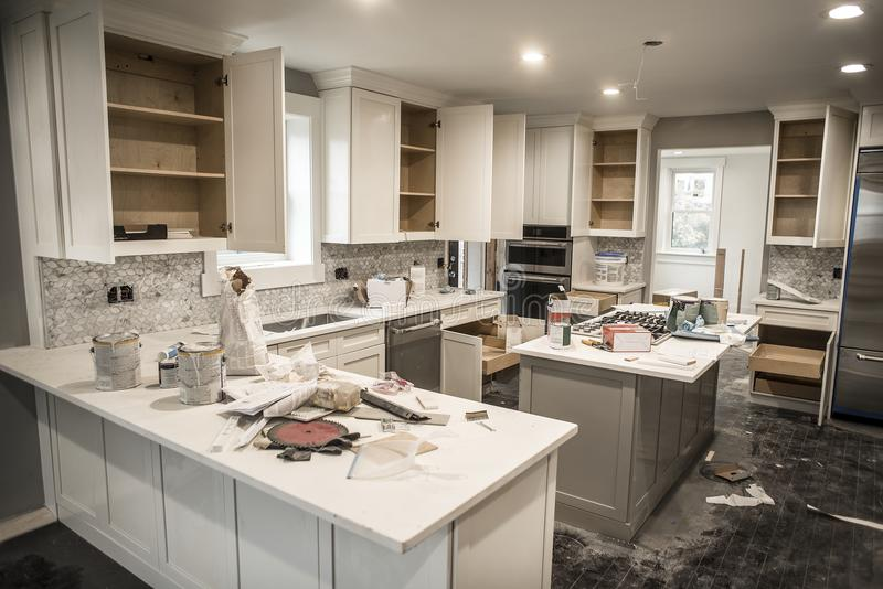 Messy home kitchen during remodeling with cabinet doors open cluttered with paint cans, tools and dirty rags, canned ceiling light royalty free stock photo