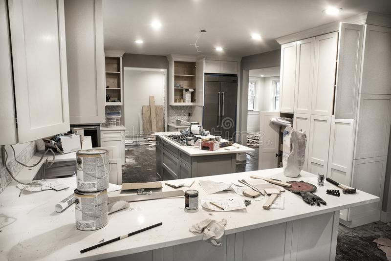 Messy home kitchen during remodeling with cabinet doors open cluttered with paint cans, tools and dirty rags stock photos