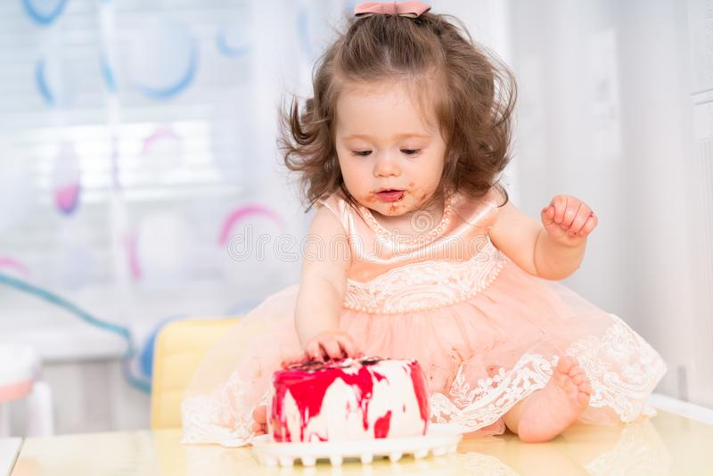 Messy little girl eating a birthday cake stock image
