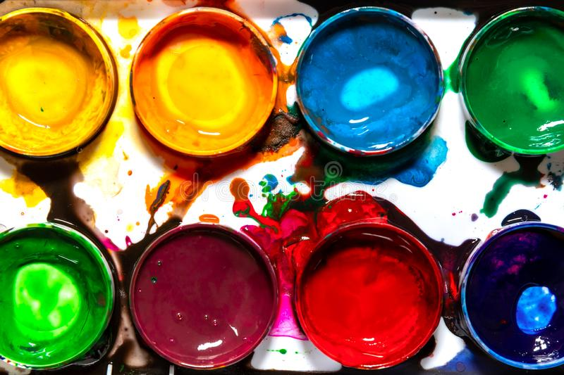 Messy palette for drawing with watercolor paints in circular forms close-up, top view, bright colorful abstract pattern of hobbies royalty free stock photography