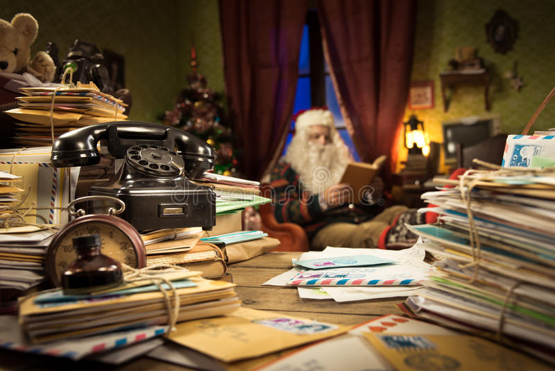 Messy Santa Claus desk. With letters and vintage phone, he is sitting on the background and reading a book royalty free stock image