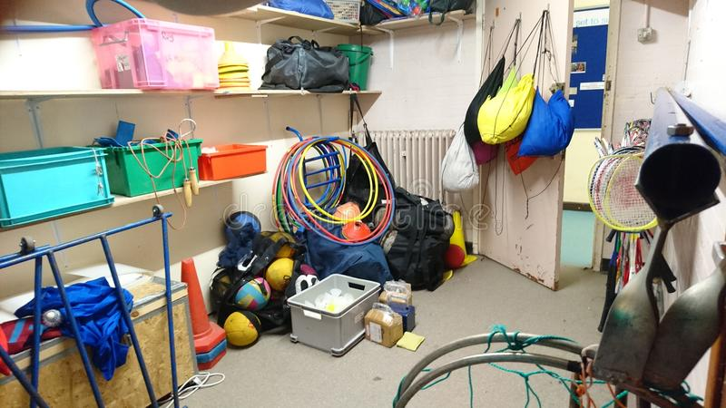 Messy school sports equipment storage area. Room unit pe physical education activity hula hoops skipping rope nets bibs balls bag boxes badminton rackets tennis stock image