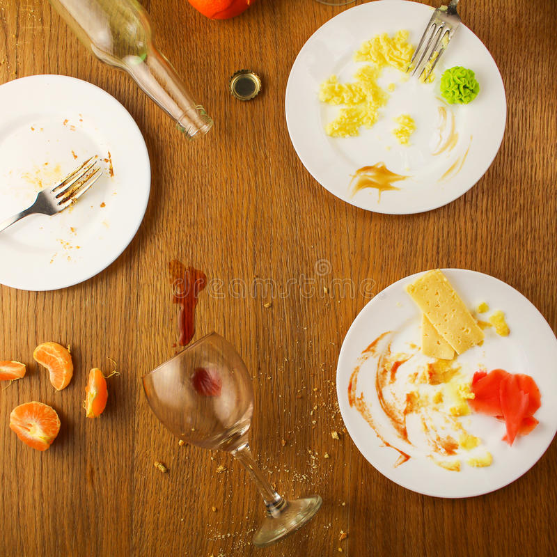 Messy table after party. Leftover food, spilled drinks. Dirty dishes stock photography