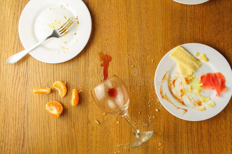 Messy table after party. Leftover food, spilled drinks, dirty dishes. Top view stock image