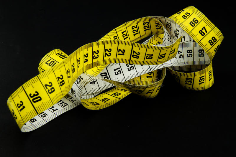 Messy tape measure on black. A yellow and white tape measure in a messy position, on a black surface royalty free stock image