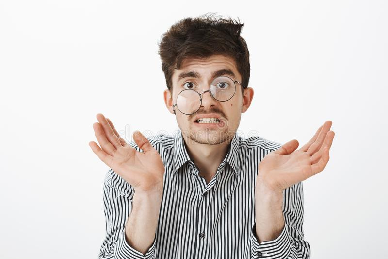 Messy untidy funny guy with moustache and beard, shrugging and raising palm, grimacing from confusion and sress, looking. Like garbage agter rough night royalty free stock photo