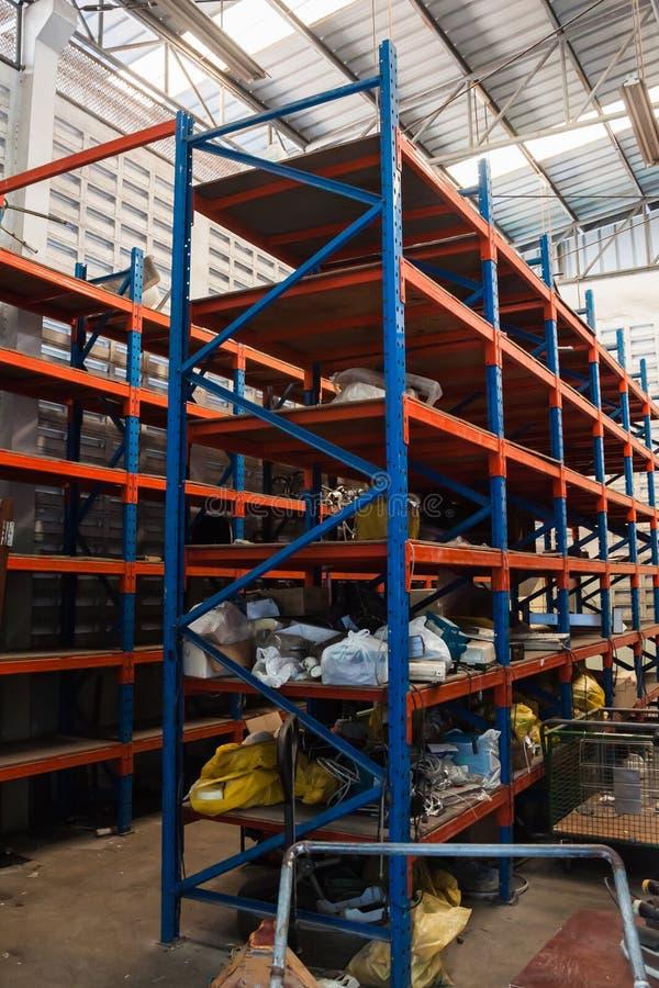 Messy warehouse storage,metal shelves racking. In warehouse stock image