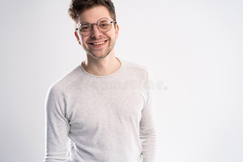 Mest bra leende som du såg någonsin Stående av den stiliga unga mannen som ser kameran med leende, medan stå mot vit arkivbilder