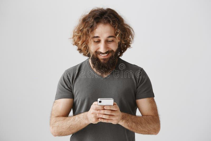 Mest bra väg av kommunikationen Stående av den nöjda och koncentrerade östliga manliga hållande smartphonen som spelar lekar elle royaltyfri bild