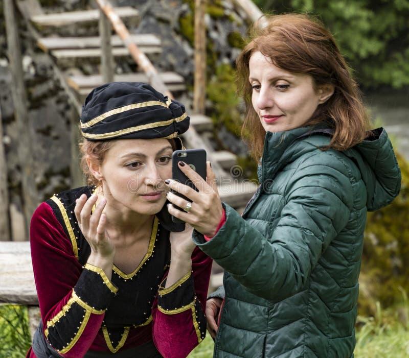 Mestia, Georgia - 11 juni 2016 - Female-modellen fixerar hennes smink med hjälp av en mobiltelefonkamera royaltyfria foton