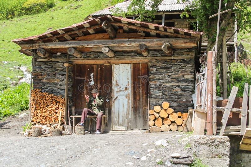 Mestia, Georgia - 06182017: Viejo hombre que habla en el teléfono fuera de la cabaña con la madera para el invierno en las mont imágenes de archivo libres de regalías