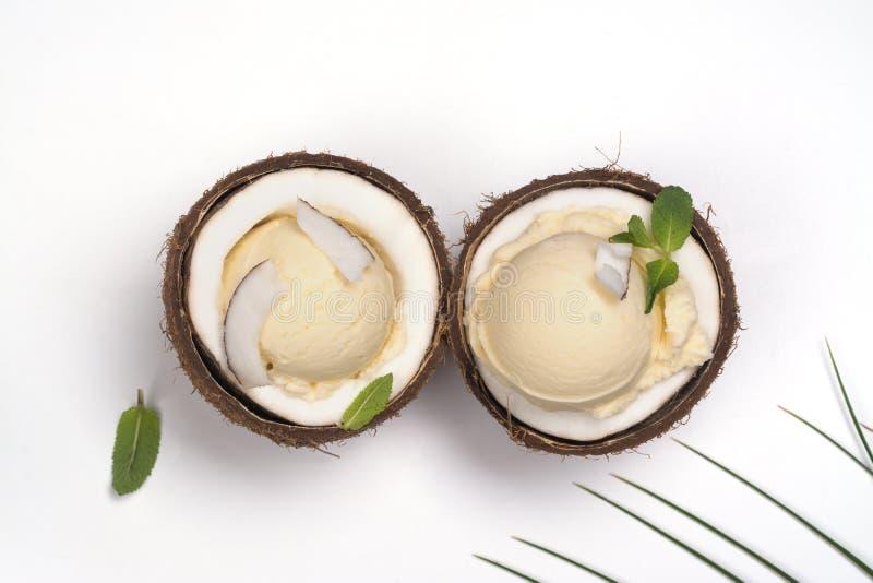 Mestoli crema del gelato al cocco a metà delle coperture della noce di cocco fotografia stock