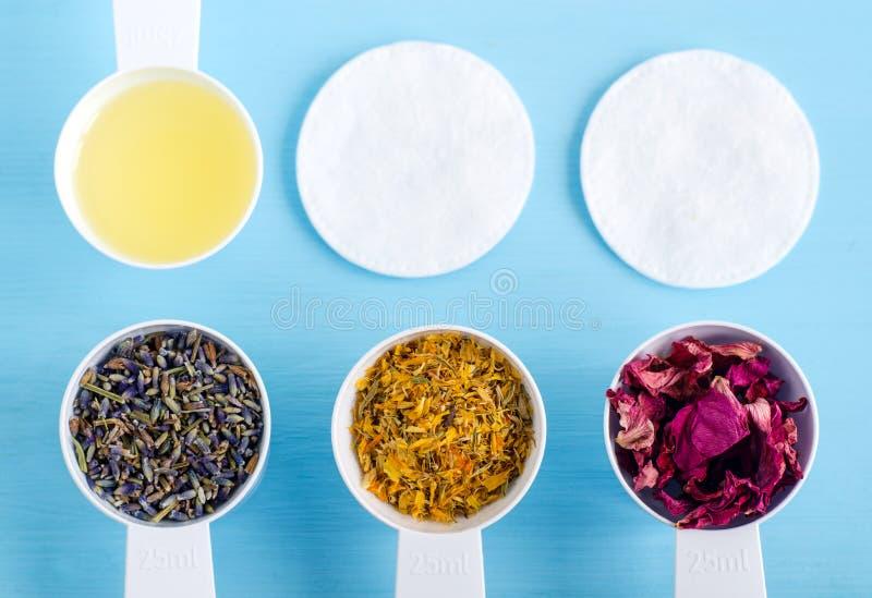 Mestoli di plastica con olio d'oliva e le varie erbe curative - fiori asciutti del tagete, della lavanda e della rosa canina Arom fotografia stock