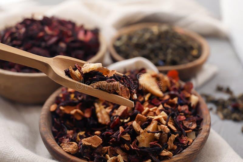 Mestolo delle foglie di tè asciutte con i frutti sopra la ciotola sulla tavola fotografia stock