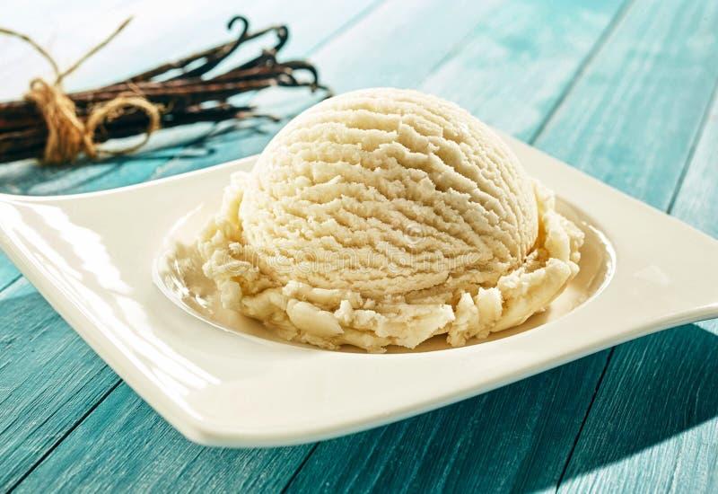 Mestolo di gelato alla vaniglia cremoso su un piatto fotografie stock
