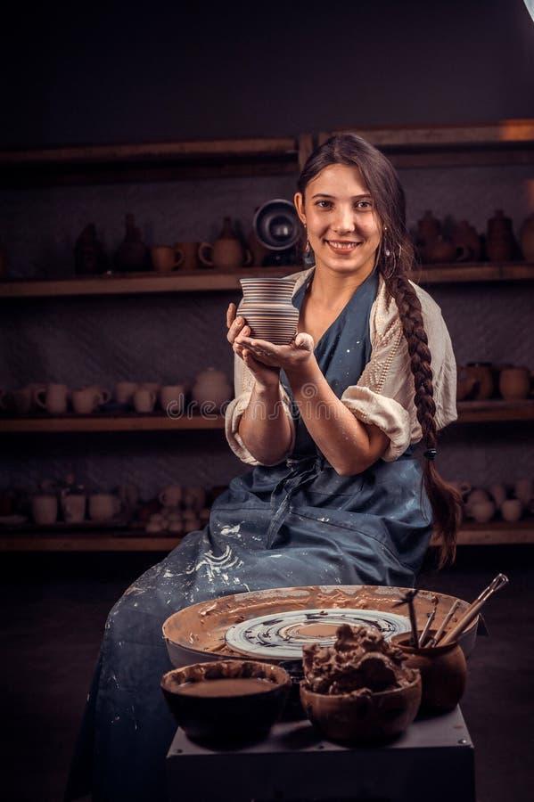 Mestre à moda da jovem mulher que levanta ao fazer o produto de cerâmica Of?cio nacional fotos de stock royalty free
