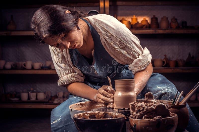 Mestre bonito do handicraftsman que faz o potenciômetro cerâmico na roda da cerâmica handcraft fotos de stock royalty free