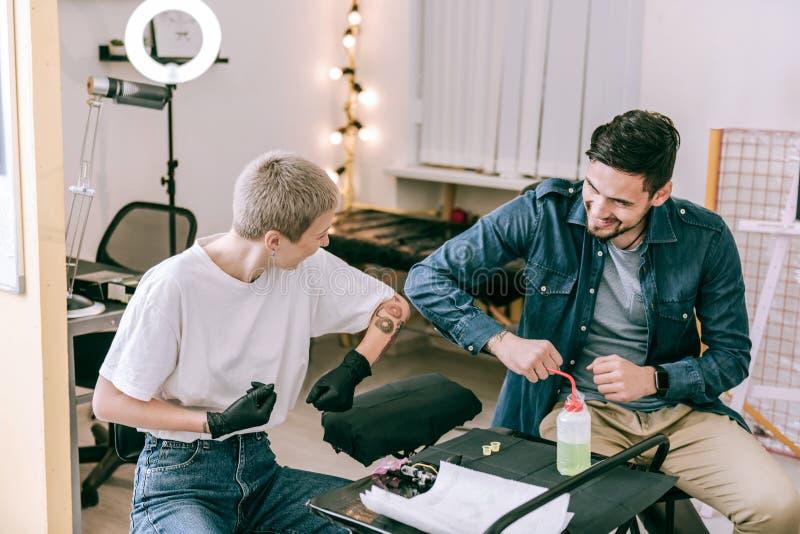 Mestre de cabelos curtos fêmea da tatuagem e seu cliente masculino que têm o grande tempo fotografia de stock royalty free