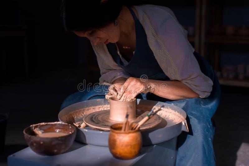 Mestre de encantamento do artesão que faz o potenciômetro cerâmico na roda da cerâmica Trabalho de m?o foto de stock