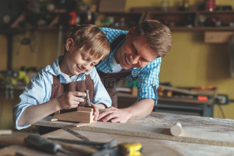 Mestre de sorriso e um rapaz pequeno no trabalho imagens de stock royalty free