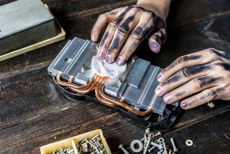 Mestre do reparo do computador com as mãos sujas escuras que limpam a parte eletrônica na tabela f foto de stock royalty free