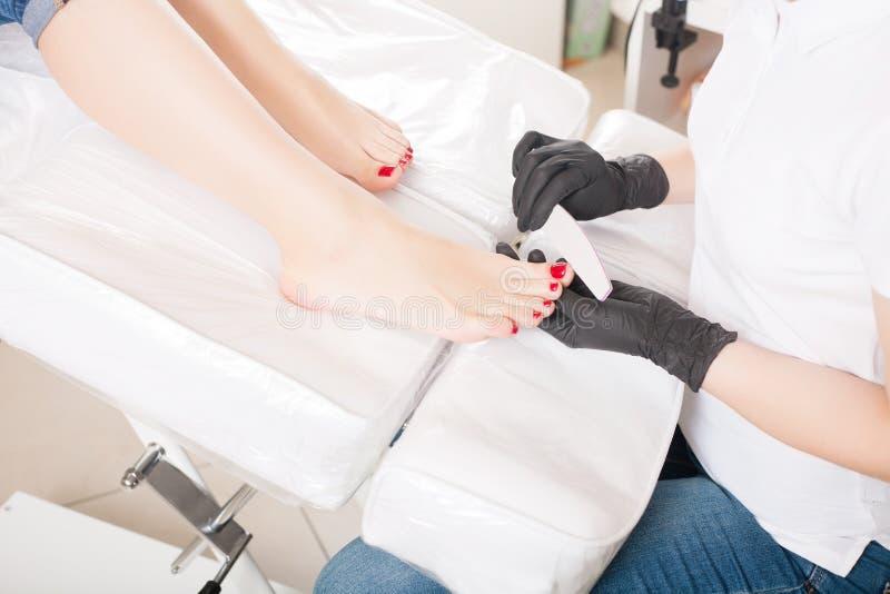 Mestre durante um pedicure O processo de pedicures profissionais imagens de stock