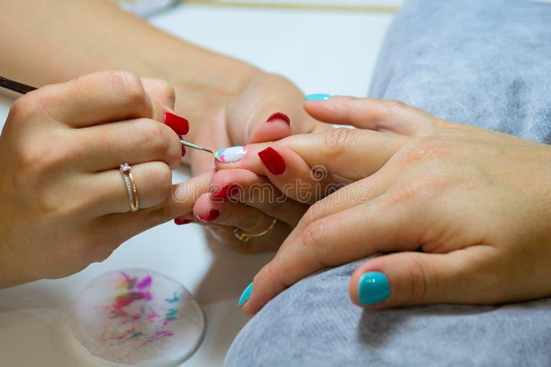 Mestre em um salão de beleza que faz a menina dos tratamentos de mãos imagem de stock