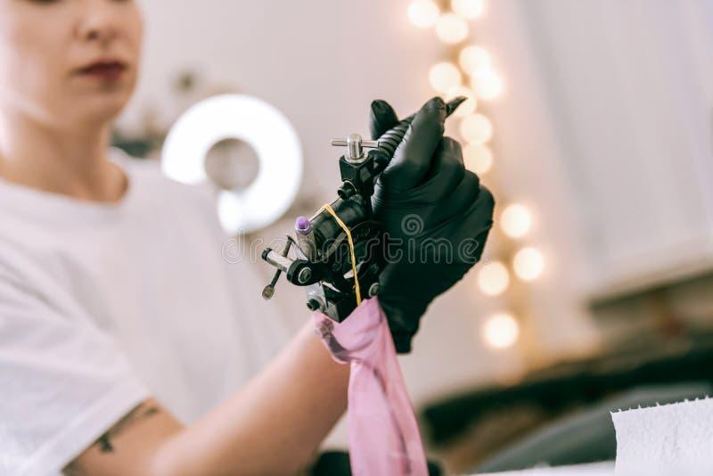 Mestre fêmea da tatuagem que guarda a máquina especial com suas mãos foto de stock royalty free