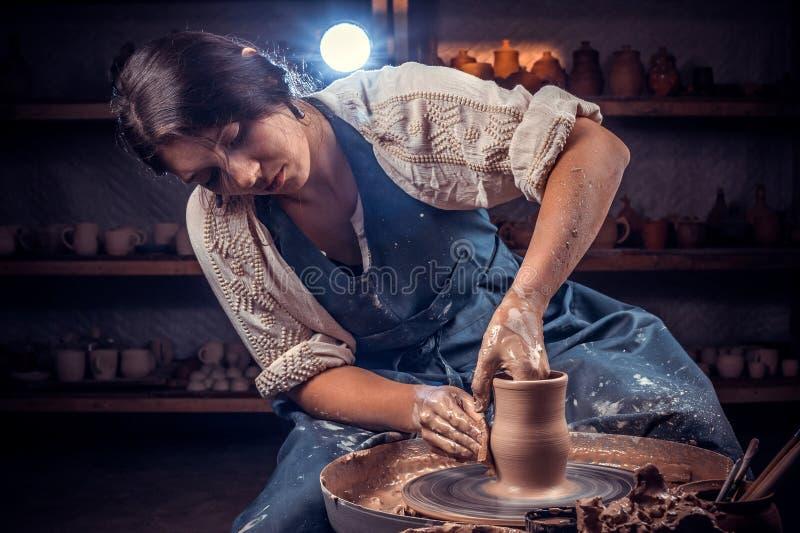 Mestre f?mea de encantamento que molda um vaso da argila em uma roda de oleiro Produ??o do artesanato imagem de stock royalty free