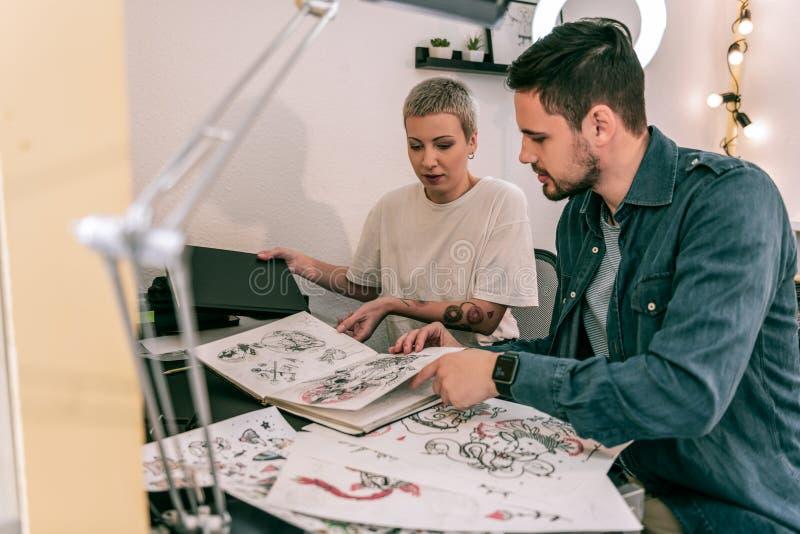 Mestre fêmea profissional da tatuagem que mostra todos seus esboços e projetos fotografia de stock