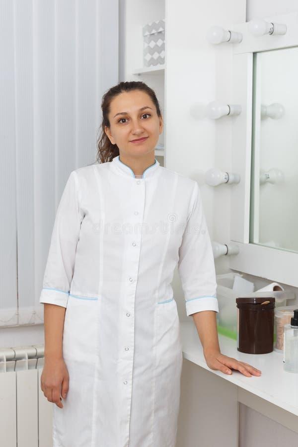 Mestre profissional da cera Est? vestindo uma veste e um sorriso brancos fotografia de stock royalty free