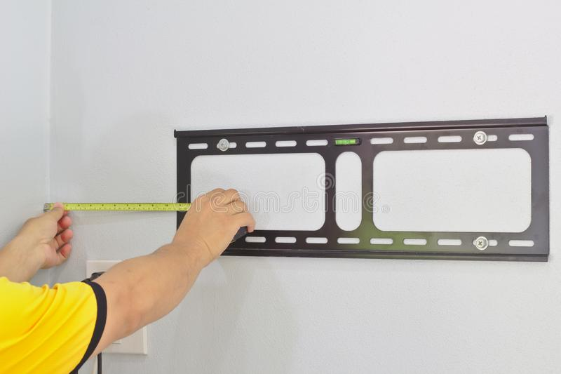 Mesuré par une distance jaune de cartouche de mètre du mur Le technicien installe le dispositif pour accrocher la TV sur le mur m photo libre de droits