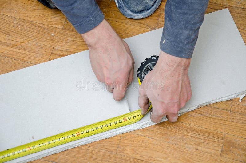 Mesurant et coupant la plaque de plâtre de gypse photo libre de droits