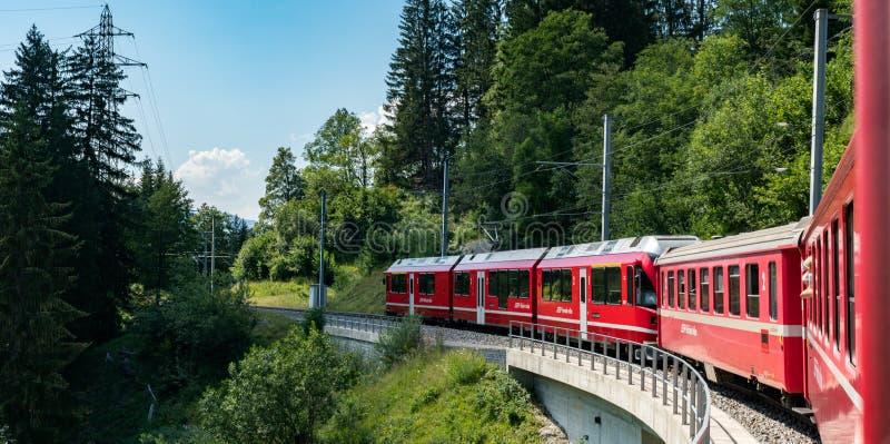 Mesure étroite rouge traincrossing au-dessus d'un pont en pierre sur un bout droit sinueux de voie dans les Alpes suisses photo stock
