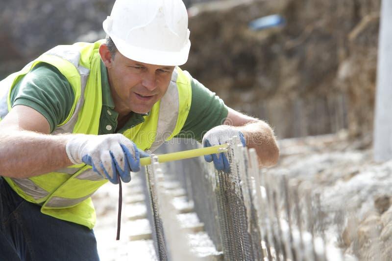 Mesure de fixation de travailleur de la construction photographie stock