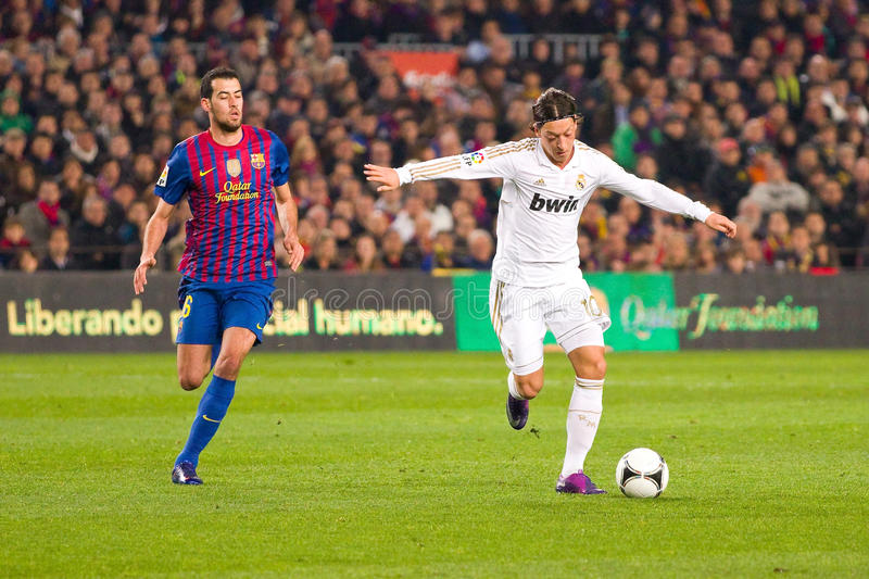 Mesut Ozil in action. BARCELONA - AUGUST 17: Mesut Ozil (R) in action during the Spanish Super Cup final match between FC Barcelona and Real Madrid, 3 - 2, on royalty free stock photo