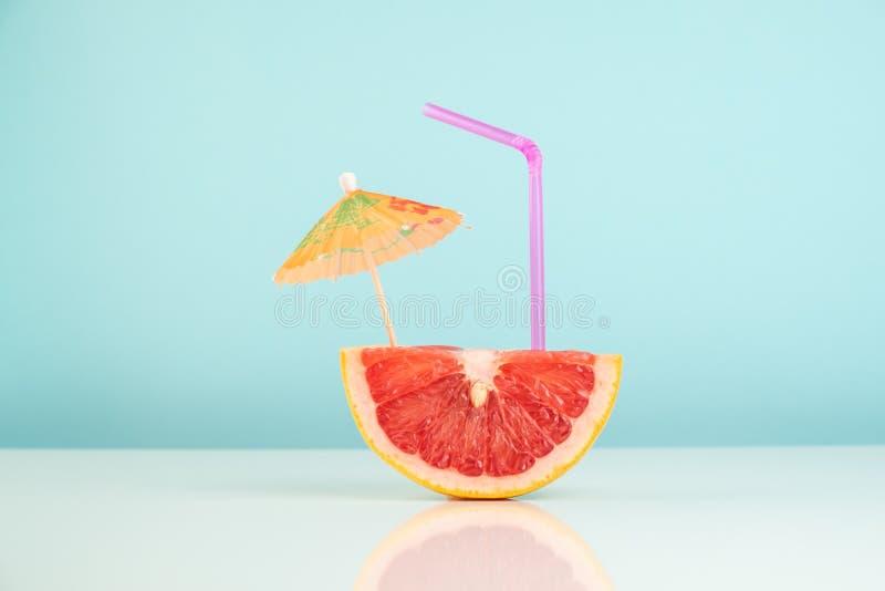 Metà del pompelmo su fondo bianco e blu, cocktai della vitamina immagine stock