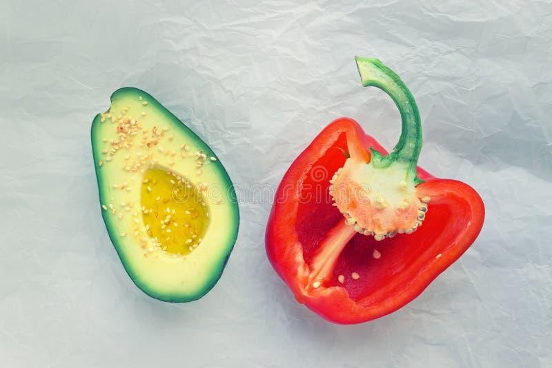Metà dell'avocado maturo e del peperone dolce rosso sulla carta pergamena fotografie stock