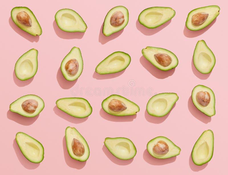 Metà dell'avocado su fondo rosa, disposizione piana fotografia stock libera da diritti