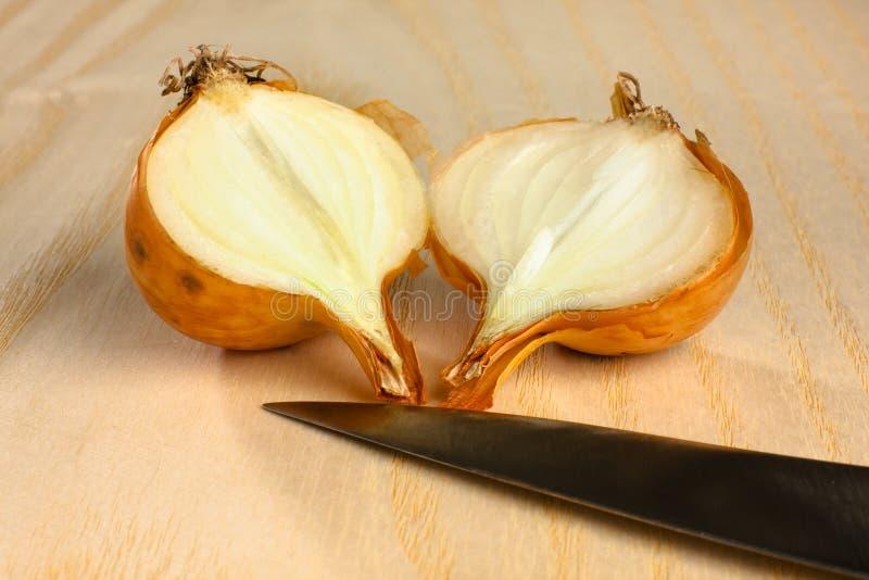 Metà della cipolla e del coltello su fondo di legno immagini stock libere da diritti