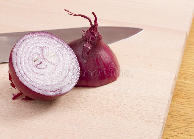 Metà della cipolla rossa con il coltello immagini stock