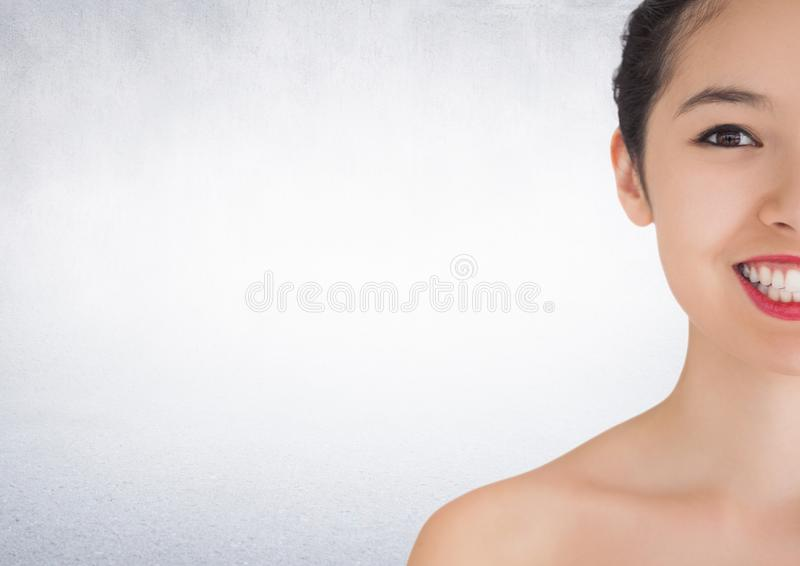 Metà della donna che sorride contro la parete bianca immagine stock