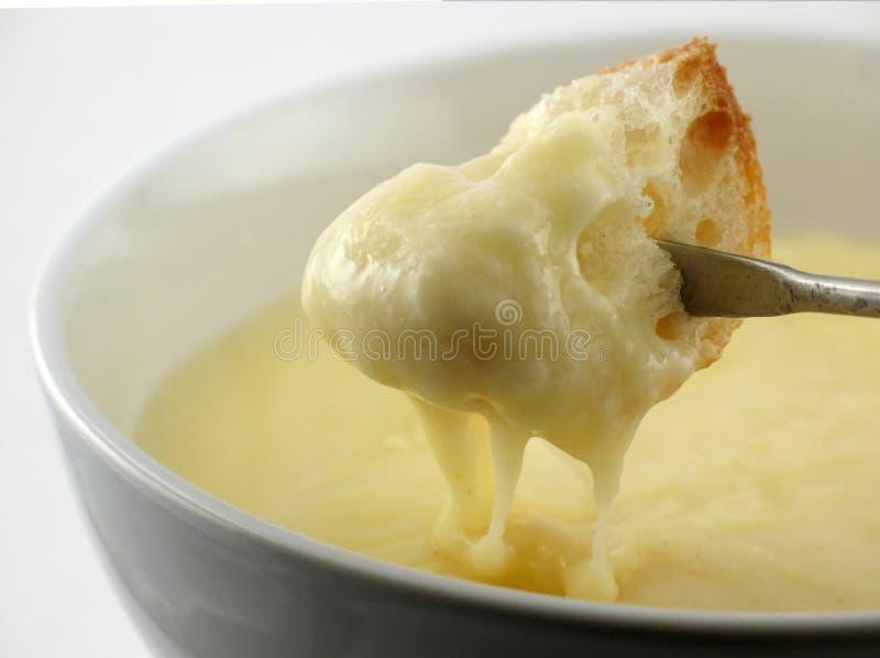 Metà della fonduta di formaggio tuffata fotografia stock
