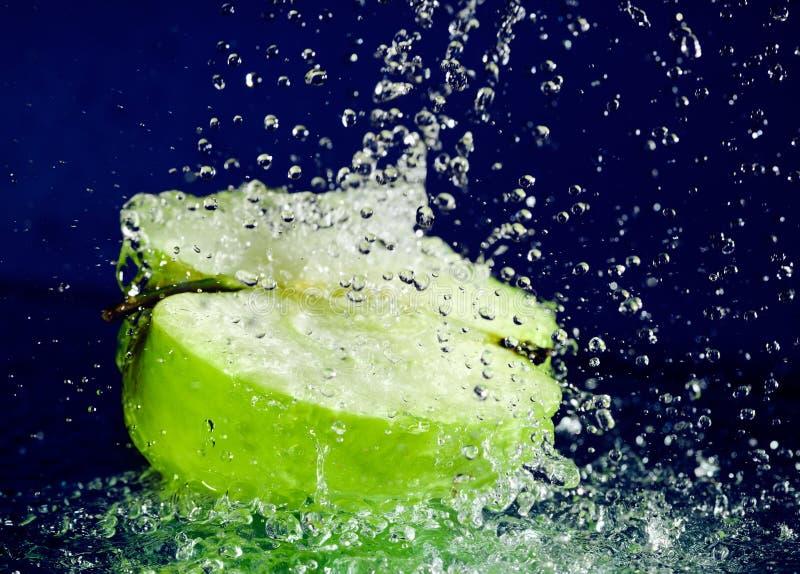 Metà della mela verde con acqua di movimento arrestato fotografie stock